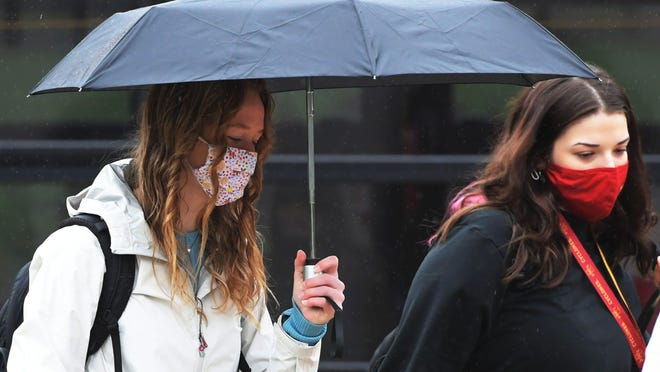 Iowa State University students walk in the university's central campus wearing face masks on Thursday.