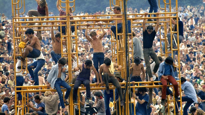 People climb and sit in the sound tower during Woodstock in Bethel, New York, August, 1969.