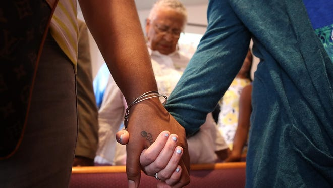 Worshipers hold hands during morning services at Mount Zion First African Baptist Church August 13, 2017 in Charlottesville, Virginia.