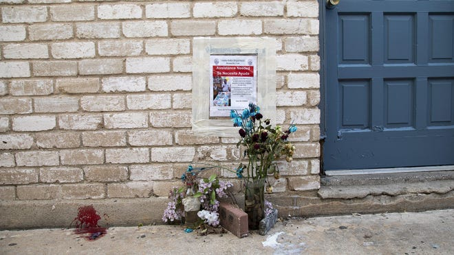 Mirla Zuñiga places candles on a small memorial that the residents of an Austin apartment complex made where Adelaido Bernabe Urias was fatally shot. He was selling ice cream treats when three men shot him during what police say was a robbery attempt.