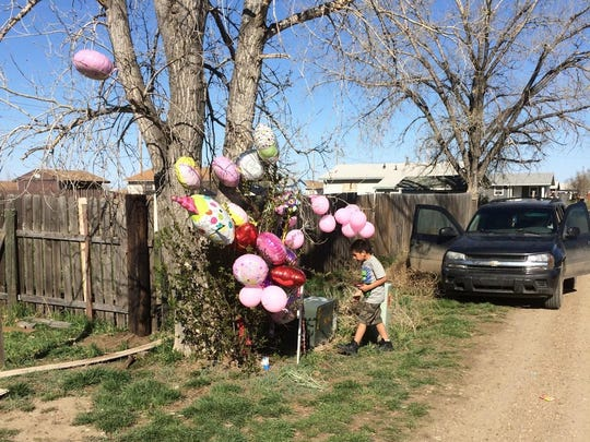 Kahlil Beauchman of Poplar places candy and a toy cellphone at a makeshift memorial site in Poplar Thursday to honor 1-year old Kenzley Olson, who was found dead after an Amber Alert on Wednesday.