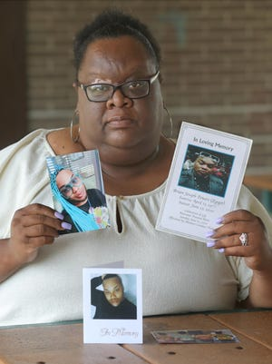 "Vivian Powers-Smith shows photos of her brother Brian ""Egypt"" Powers on Thursday in Akron."