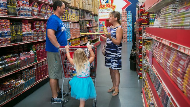 Jackie and Eddie Pike shop for fireworks with their three-year-old daughter Jessica on Wednesday at Sky King Fireworks in south Fort Myers.
