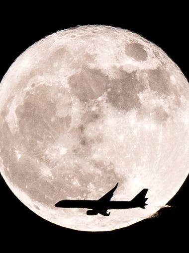 A plane crosses the outline of the supermoon on Nov. 14, 2016.