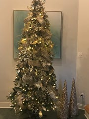 A tall, elegant tree features gold and white and plenty