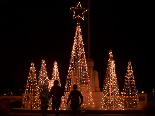 Runners are silhouetted in front of the fountain before the Bright Lights for Easterseals 5K run and 1-mile walk at Ritzy's Fantasy of Lights in Garvin Park in Evansville, Ind., on Wednesday, Nov. 29, 2017. On Wednesday only, Ritzy's Fantasy of Lights, the fundraiser for Easterseals Rehabilitation Center, was closed to cars to make way for runners and walkers. Ritzy's Fantasy of Lights is open nightly through New Year's Day, Sunday through Thursday: 5 p.m. - 9 p.m., and Friday--Saturday 5 p.m. - 10 p.m.