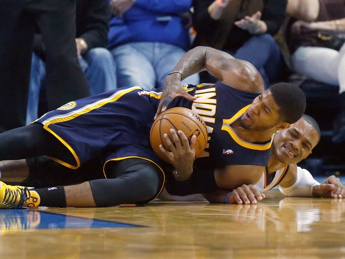 Indiana Pacers forward Paul George (24) keeps the ball away from Oklahoma City Thunder guard Russell Westbrook (0) in the third quarter of an NBA basketball game in Oklahoma City, Sunday, Dec. 8, 2013. Oklahoma City won 118-94. (AP Photo/Sue Ogrocki)