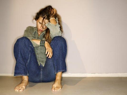 Unhappy woman sitting on floor