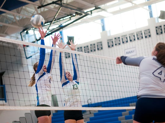 Pioneers Sydney Soper and Devyn Gordon reach high for the ball Monday, Oct. 31, during district volleyball action at Croswell Lexington High School.