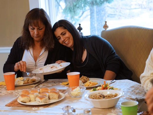 Terry Marrongelli serves herself some turkey as her 26 year-old daughter Jenna rest her head on her mother's shoulder during Thanksgiving dinner at the Limen House where Jenna is currently living in recovery.