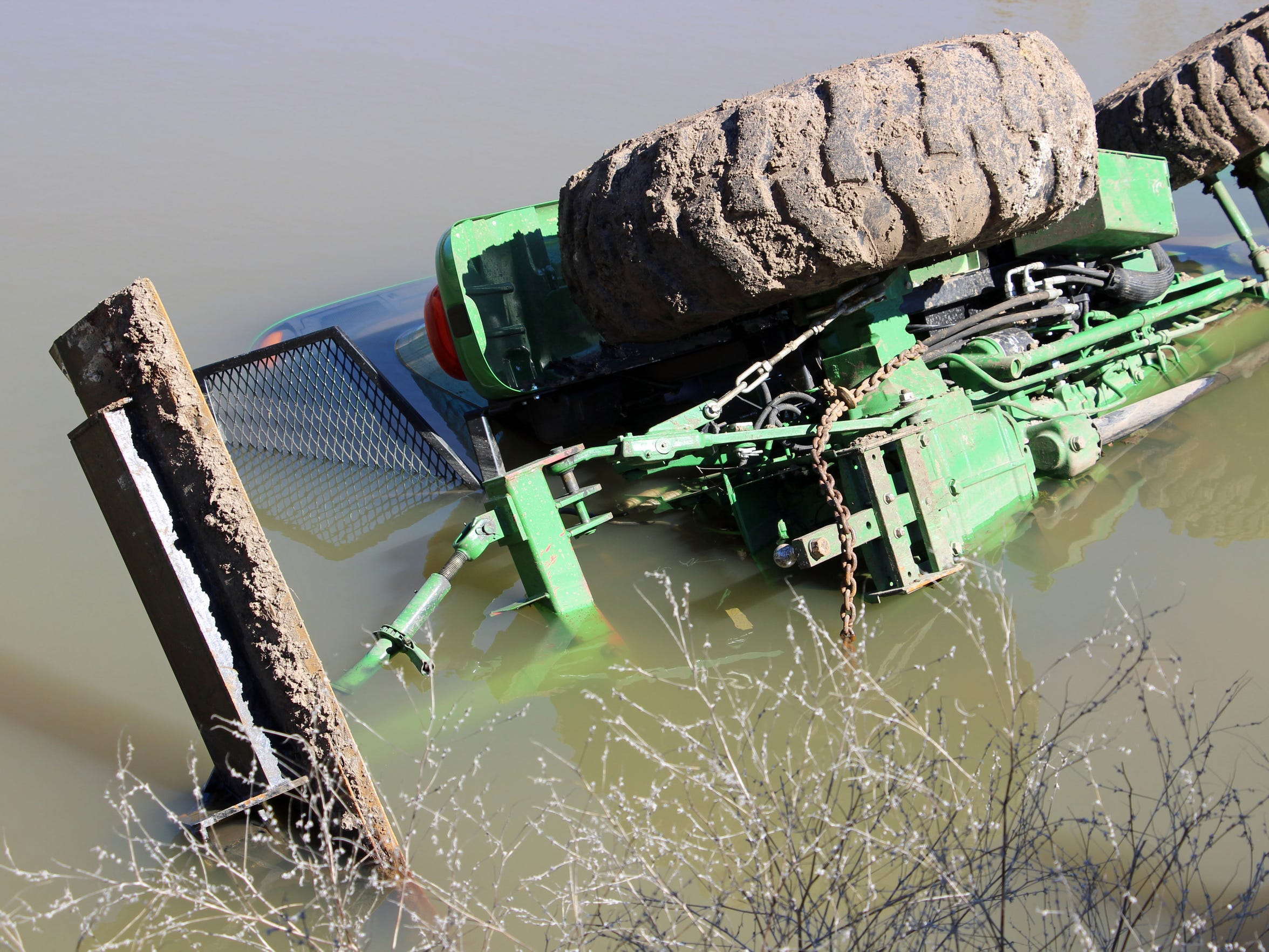 A picture of the tractor a day later shows how far the water level dropped compared to the night Eldon Cooper was rescued from the cab of the tractor after it rolled and flipped, trapping him inside the submerged cab.