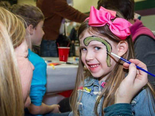 Molly Flint of Oconomowoc sits for a face painting from her mother, Linda, during a past edition of the St. Joan of Arc Parish School Carnival in Nashotah. In addition to face painting the carnival also has games, food, a cake walk, a fortune teller and more.