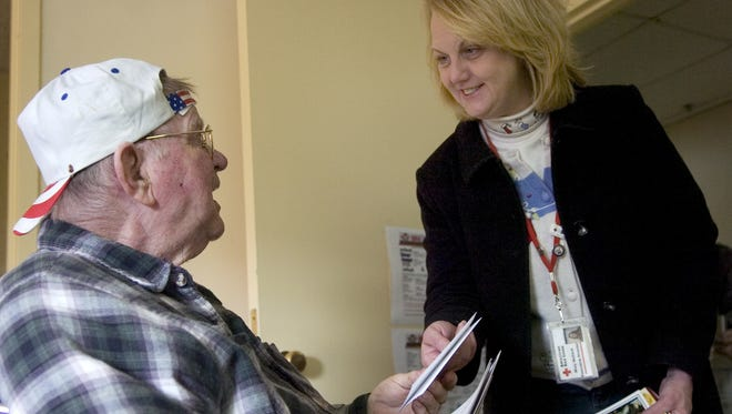 Mary McCord of the American Red Cross gives greeting cards to Evan Hodge Jr. at the Chillicothe Veterans Affairs Medical Center in this 2008 photo. The cards were sent from across the nation and delivered to veterans by volunteers from the American Red Cross and participants in the Big Brothers Big Sisters program.