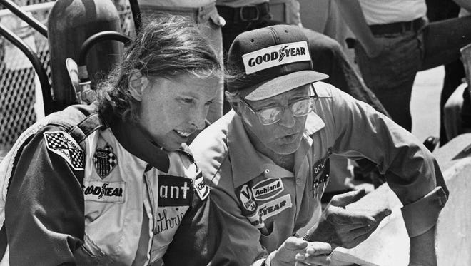 Janet Guthrie with car owner Rolla Vollstedt sitting on pit wall.
