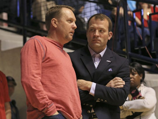 Athletic director Ross Bjork, right, speaks with former football coach Hugh Freeze at a basketball game in this archive photo.