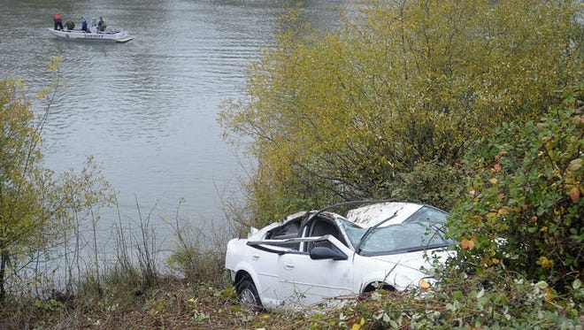 The Benton County Sheriff Marine Patrol watches from the Willamette River as a Chrysler Sebring was removed from the river next to Highway 20 near the south entrance of Hewlett-Packard on Friday morning.