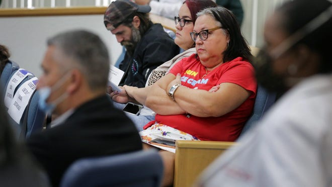 Opponents of coronavirus restrictions sit unmasked Friday as county commissioners in West Palm Beach finalize plans to reopen beaches, starting Monday.