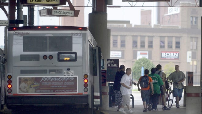 DAVID ZALAZNIK/JOURNAL STAR FILE PHOTO  Riders make their way to and from buses at the CityLink Transit transfer station in Downtown Peoria.