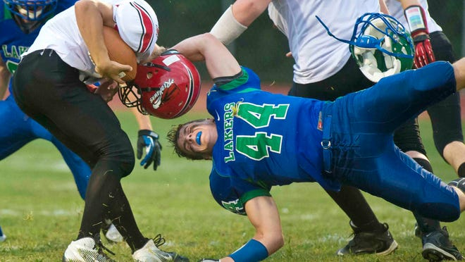 Colchester's Grant Cummings (right) loses his helmet as he tackle Champlain Valley'S Andrew Bortnick during a game on Aug. 30, 2013.