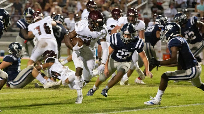 Benedictine's Justin Thomas (4) runs for a gain as Effingham County's Luke Roberts (27) attempts to tackle him on Friday night in Springfield. Benedictine won 49-7.