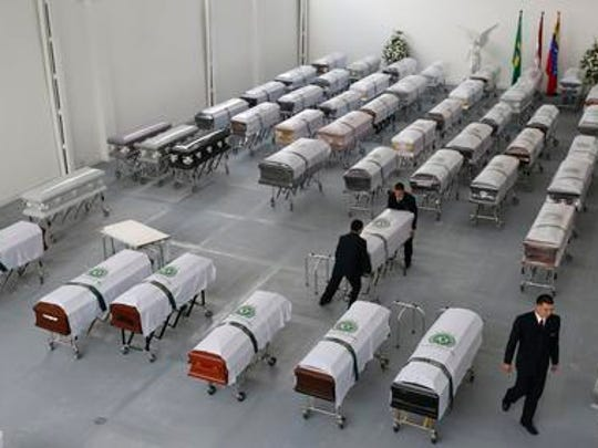 Funeral employees ready caskets covered in white sheets with a Chapecoense soccer team logo that contain the remains of team members at the San Vicente funeral home in Medellin, Colombia, Friday, Dec. 2, 2016. The bodies of the Brazilian victims of this week's air tragedy will be repatriated later Friday to Chapeco, the hometown of the Brazilian soccer team. Members of the team and a group of journalists who perished on the flight were headed to the Copa Sudamericana finals when the plane ran out of fuel, crashing into the Andes outside Medellin.