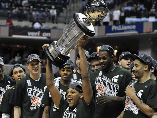 MSU's Adreian Payne screams as he raises the Big Ten Tournament Championship trophy as he celebrates with teammates after the Spartans beat Ohio State 68-64 in Indianapolis  Sunday 3/11/2012.