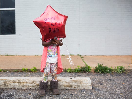 "Dorshae Harkness, 3, holds a balloon that says ""Rest Easy Rann"" during the vigil for Randy Smith on the one-year anniversary of his fatal shooting on Thursday, March 30, 2017, in Anderson."