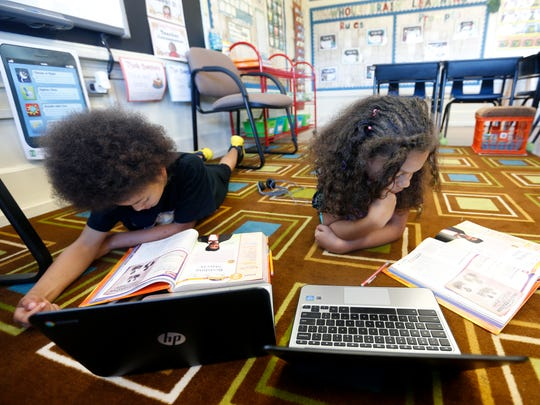 Fifth-graders at York Elementary Keymond Brown (left), 11, and Elizabeth Russell, 11, read from their text books on the floor as they complete an assignment on Thursday, May 6, 2016.