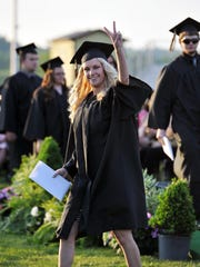 River View graduating senior Mackenzie Holbrook celebrates after receiving her diploma by giving a peace sign to family and friends in the bleachers during the 50th commencement ceremony Sunday evening.