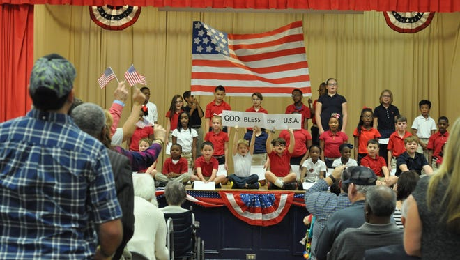 """Cherokee Elementary students sing """"Proud To Be An American"""" during the school's Veterans Day celebration held Thursday."""
