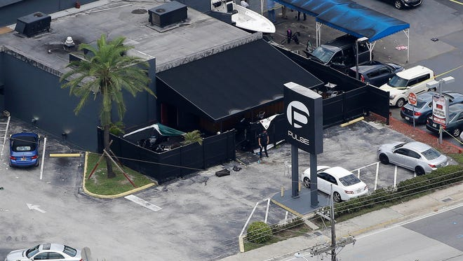 Law enforcement officials work at the Pulse nightclub in Orlando.