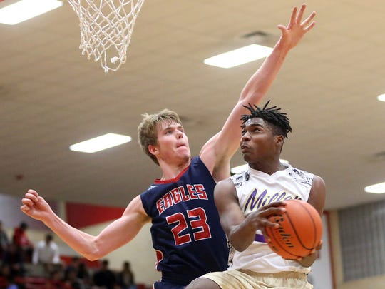 Miller's Justice Watson takes the ball to the basket against Veterans Memorial's Will Chayer during the District 30-5A championship Thursday, Feb. 16, 2017, at Ray High School in Corpus Christi.