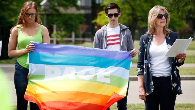 """Corning Community College student Ashley Miller, of Avoca, and CCC alumnus Dakota Carr hold a rainbow flag with """"PACE"""" written on it while CCC professor Sandy Turner-Vicioso welcomes a crowd to the Orlando vigil at the school's flagpole Thursday."""