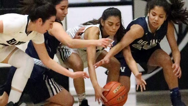 Valerie Hernandez, left, and Jackie Maciel, center, of Hank,s battle for control of the ball during with Del Valle's Alexa Rucobo and Bernie Duchene, far right, during their game Tuesday night at Hanks.