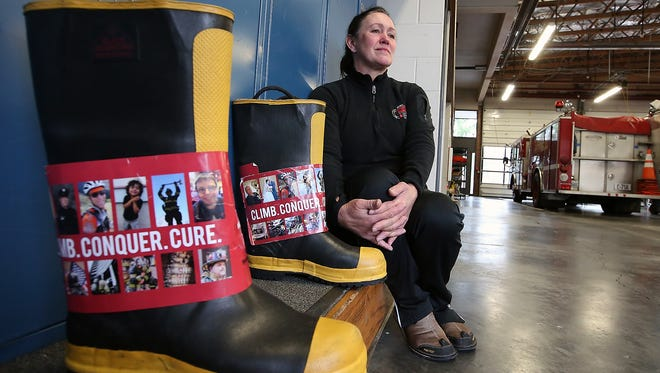 Jaunitta Lang at Poulsbo Fire Department's Station 71 on Thursday, with the boots that she used to collect donations for the upcoming Scott Firefighter Stairclimb benefiting the the Leukemia & Lymphoma Society. Lang was diagnosed with leukemia late last year. She is participating in Sunday's fundraiser, as she has in previous years.