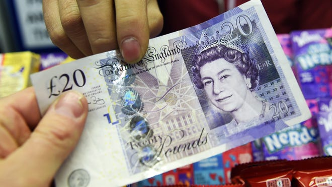A customer hands over a 20 GBP note at a store in London.