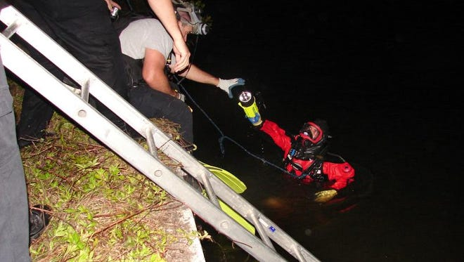 A dive technician with the Cape Coral Police Department searches a canal late Sunday.