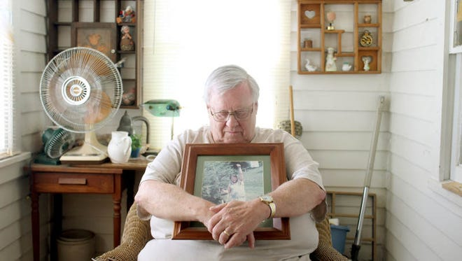 """Carl DeWoody, 76, looks down at the most recent photograph of his son, Lance, at his Olin, IA home on Thursday, May 10, 2012. """"He had no enemies"""" remarked DeWoody about his son, who was 22 years-old at the time of his death. The invesitagtion in the murder of Lance DeWoody remains open."""