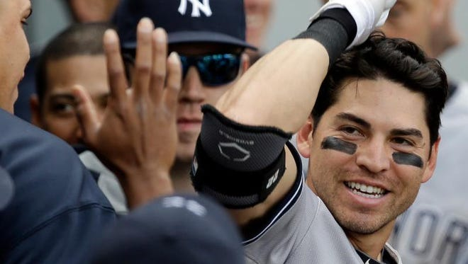 Jacoby Ellsbury #22 of the New York Yankees is greeted by teammates in the dugout after hitting a solo home run in the 10th inning against the Chicago White Sox as he crosses the plate at U.S. Cellular Field on May 24, 2014 in Chicago, Illinois. The Yankees defeated the White Sox 4-3 in 10 innings. (Photo by Jonathan Daniel/Getty Images)