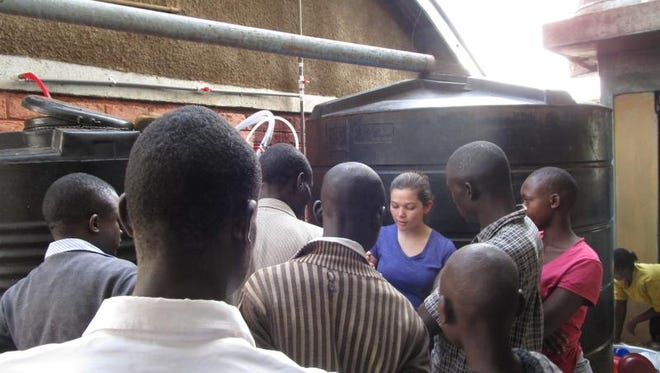 Emma Rider helps teach the men in a Kenya village about the water chlorinator and how to properly maintain it.