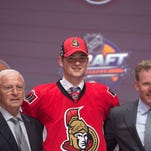 Logan Brown, second from left, stands with members of the Ottawa Senators management team Friday at the NHL draft in Buffalo.