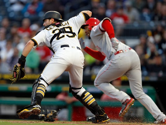 Pittsburgh Pirates catcher Francisco Cervelli (29) throws to second base as Cincinnati Reds starting pitcher Amir Garrett takes off for first after attempting a bunt with Reds' Tucker Barnhart on first in the third inning of a baseball game Wednesday, April 12, 2017, in Pittsburgh. Barnhardt was out on the throw and Garrett out at first, completing a double play. (AP Photo/Keith Srakocic)