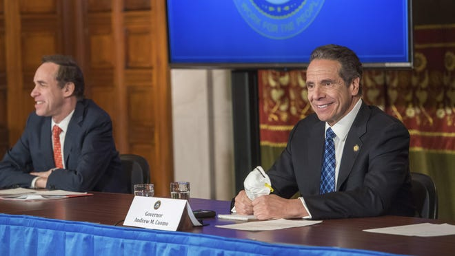 In this April 24, 2020, photo provided by the Office of Governor Andrew Cuomo, Gov. Andrew Cuomo addresses the media while holding an n95 mask during his daily press briefing on COVID-19 at the State Capitol in Albany, N.Y. At left is Dr. Howard Zucker, commissioner of the state Department of Health.