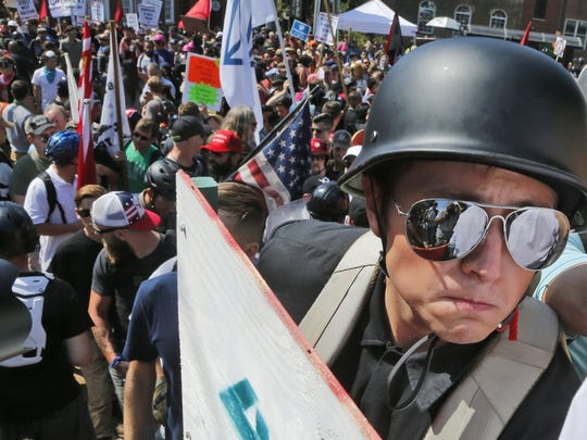 A white nationalist demonstrator with a helmet and shield walks into Lee Park in Charlottesville, Virginia, Saturday, Aug. 12, 2017. Violence erupted at the white nationalist rally (AP Photo/Steve Helber).