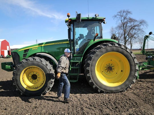 Custom farmer Bob Dorr climbs down from the tractor