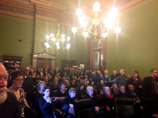A large crowd jammed an Iowa Capitol committee room Monday as a three-member Senate panel advanced a bill declaring that life begins at conception.