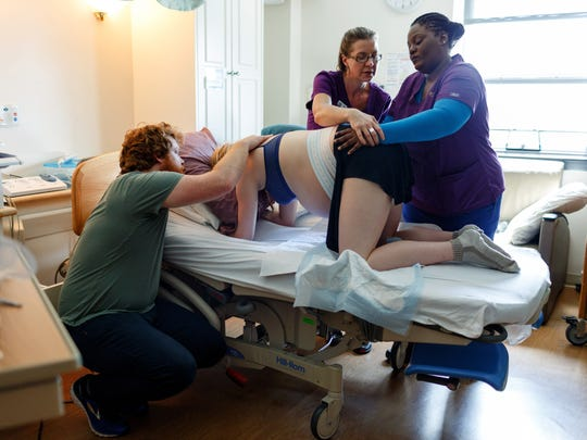 Zach Shakelford supports his partner, Maggie Hague-Shackelford, during labor as Cindy Smart, right, learns the skills of the trade from doula trainer Chama Woydak.