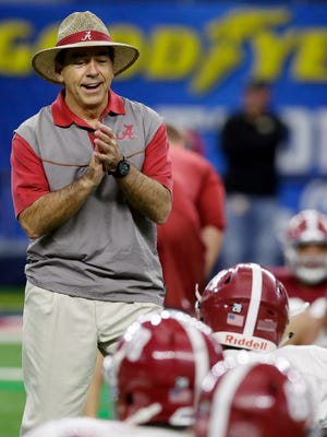 Alabama head coach Nick Saban jokes with players during team practice for the NCAA Cotton Bowl college football game against Michigan State.