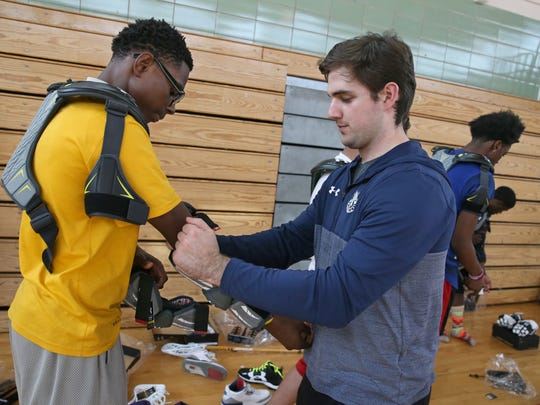Rochester Knighthawks player Luke Laszkiewicz, right, helps East eighth grader Jahmeir Warfield put on his new elbow pads at East High School Tuesday, April 11, 2017.  The Knighthawks donated Under Armour gear to the high school lacrosse team as part of their ongoing program of starting boys and girls varsity lacrosse in the city next school year.
