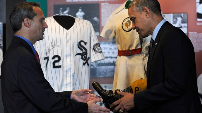 President Barack Obama is handed Joe DiMaggio's well-worn baseball glove by Baseball Hall of Fame President Jeff Idelson during a tour of the Baseball Hall of Fame in Cooperstown on Thursday. Obama visited the museum to highlight tourism and steps to help spur international visits to the 50 states. An autographed Carlton Fisk Chicago White Sox jersey is behind them.
